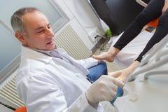 Η γυναίκα λαμβάνει την εξέταση ποδιών από το φορημένο γάντια podiatrist Στοκ φωτογραφία με δικαίωμα ελεύθερης χρήσης