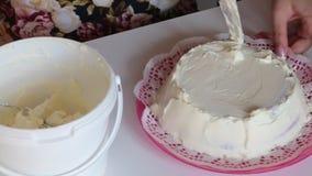 Η γυναίκα λερώνει το κέικ σφουγγαριών με την κρέμα Εφαρμόστε ένα στρώμα της κρέμας σε όλες τις πλευρές Εδώ κοντά είναι ένας κάδος απόθεμα βίντεο