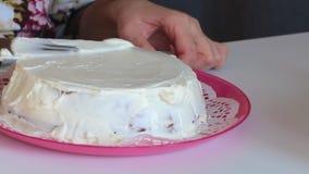 Η γυναίκα λερώνει το κέικ σφουγγαριών με την κρέμα Εφαρμόστε ένα στρώμα της κρέμας σε όλες τις πλευρές φιλμ μικρού μήκους