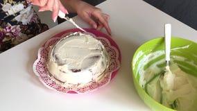 Η γυναίκα λερώνει το κέικ σφουγγαριών με την κρέμα Εφαρμόστε ένα στρώμα της κρέμας σε όλες τις πλευρές απόθεμα βίντεο