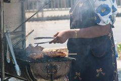 Η γυναίκα μαγειρεύει τα brochettes κοτόπουλου στη σχάρα στην οδό στοκ φωτογραφία