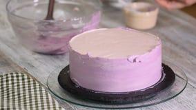 Η γυναίκα μαγειρεύει το κέικ βακκινίων Η γυναίκα λερώνει ένα κέικ με την κρέμα σε έναν άσπρο ξύλινο πίνακα απόθεμα βίντεο