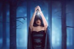 Η γυναίκα μαγισσών με το μαύρο επενδύτη κρατά το μαχαίρι υψηλό και είναι έτοιμη Στοκ φωτογραφία με δικαίωμα ελεύθερης χρήσης