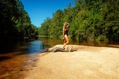 Η γυναίκα μαγιό επάνω ο φραγμός άμμου σύνδεσης στοκ φωτογραφίες
