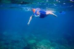 Η γυναίκα μαθαίνει να κολυμπά με αναπνευτήρα στην πλήρη μάσκα προσώπου Το υποβρύχιο τοπίο κοραλλιών και κολυμπά με αναπνευτήρα Στοκ Εικόνα