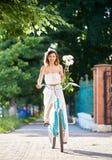 Η γυναίκα μαριονετών οδηγά ένα εκλεκτής ποιότητας ποδήλατο με την ανθοδέσμη των peonies στοκ φωτογραφία με δικαίωμα ελεύθερης χρήσης