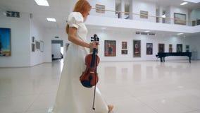 Η γυναίκα με ένα βιολί περπατά κατά μήκος του γκαλεριού τέχνης απόθεμα βίντεο