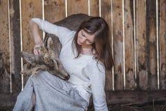 Η γυναίκα με ένα ελάφι μωρών σε μια μάνδρα φροντίζει και παίρνει την προσοχή Στοκ Εικόνα