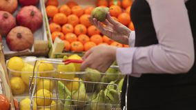 Η γυναίκα με ένα κάρρο αγορών κάνει τις αγορές στα φρούτα φιλμ μικρού μήκους