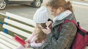 Η γυναίκα με ένα μικρό κορίτσι κάθεται σε έναν πάγκο και χρησιμοποιεί τις συσκευές απόθεμα βίντεο