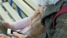 Η γυναίκα με ένα μικρό κορίτσι κάθεται σε έναν πάγκο και χρησιμοποιεί τις συσκευές φιλμ μικρού μήκους