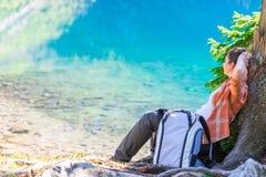 η γυναίκα με ένα σακίδιο πλάτης χαλαρώνει και στηρίζεται από τη λίμνη Στοκ φωτογραφίες με δικαίωμα ελεύθερης χρήσης