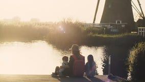 Η γυναίκα με δύο παιδιά κάθεται σε μια αποβάθρα λιμνών στο ηλιοβασίλεμα Καταπληκτικός πυροβολισμός μιας οικογένειας μαζί κοντά στ φιλμ μικρού μήκους