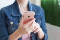 Η γυναίκα με τα ακουστικά που κρατά στο χέρι iPhone6S αυξήθηκε χρυσός Στοκ Φωτογραφίες