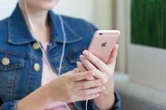 Η γυναίκα με τα ακουστικά που κρατά το iPhone 6 S αυξήθηκε χρυσός Στοκ φωτογραφία με δικαίωμα ελεύθερης χρήσης