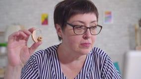 Η γυναίκα με τα γυαλιά που κάθεται σε έναν πίνακα στο καθιστικό που κρατά μια ενίσχυση ακρόασης χρησιμοποιεί στενό έναν επάνω lap φιλμ μικρού μήκους