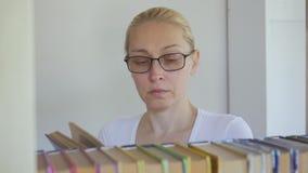 Η γυναίκα με τα γυαλιά στη βιβλιοθήκη ψάχνει μεταξύ των βιβλίων στο ράφι απόθεμα βίντεο