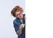 Η γυναίκα με τα κόκκινα γυαλιά παρουσιάζει στο έμβλημα Στοκ Φωτογραφία