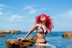 Η γυναίκα με τα κόκκινα τριχώματα είναι ευτυχής στην παραλία Στοκ Φωτογραφία