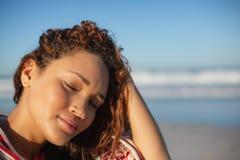 Η γυναίκα με τα μάτια έκλεισε τυλιγμένος στη γενική συνεδρίαση στην παραλία στην ηλιοφάνεια στοκ φωτογραφίες