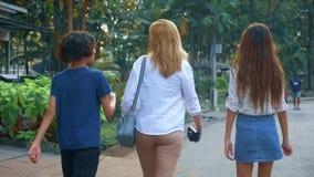 Η γυναίκα με τα παιδιά, τους εφήβους γιων και κορών με μια κάμερα περπατά μέσω των οδών μιας μεγάλης σύγχρονης πόλης στοκ εικόνα με δικαίωμα ελεύθερης χρήσης