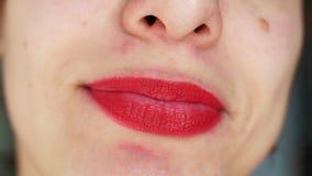 Η γυναίκα με τα φωτεινά κόκκινα χείλια χαμογελά ευρέως Κινηματογράφηση σε πρώτο πλάνο απόθεμα βίντεο