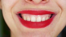 Η γυναίκα με τα φωτεινά κόκκινα χείλια χαμογελά ευρέως Κινηματογράφηση σε πρώτο πλάνο φιλμ μικρού μήκους