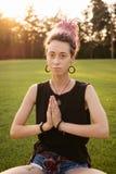Η γυναίκα με τα dreadlocks που κάνουν τη γιόγκα ασκεί υπαίθρια Στοκ φωτογραφία με δικαίωμα ελεύθερης χρήσης