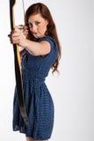 Η γυναίκα με την κόκκινη τρίχα παίρνει το στόχο με το βέλος Στοκ Φωτογραφίες