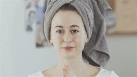Η γυναίκα με την πετσέτα στο κεφάλι που εφαρμόζει ένα λοσιόν πετρελαίου στο πρόσωπό της και εξετάζει τη κάμερα απόθεμα βίντεο