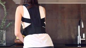 Η γυναίκα με την τραυματισμένη πλάτη φορά πίσω τον επίδεσμο υποστήριξης απόθεμα βίντεο