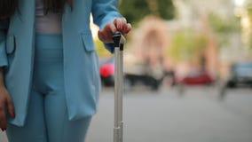 Η γυναίκα με τη βαλίτσα κάνει την περιμένοντας χειρονομία χεριών απόθεμα βίντεο