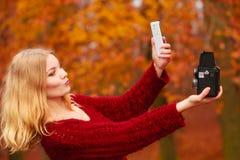 Η γυναίκα με τη κάμερα και το smartphone παίρνουν selfie τη φωτογραφία Στοκ Εικόνα