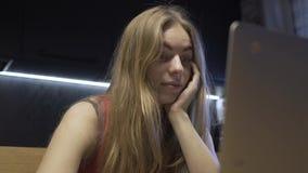 Η γυναίκα με τη συναισθηματική έκφραση του προσώπου εξετάζει το όργανο ελέγχου lap-top απόθεμα βίντεο