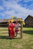 Η γυναίκα με τον άνδρα, που ντύνεται στα ρωσικά λαϊκά κοστούμια, στέκεται κοντά σε έναν του χωριού φράκτη Στοκ εικόνες με δικαίωμα ελεύθερης χρήσης