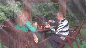 Η γυναίκα με τον άνδρα κάθεται κοντά στον πίνακα με το κάψιμο των κεριών και τρώει τα τρόφιμα φιλμ μικρού μήκους
