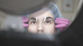 Η γυναίκα με τον κυβερνήτη brow εξετάζει στον καθρέφτη τη δερματοστιξία στο σαλόνι απόθεμα βίντεο
