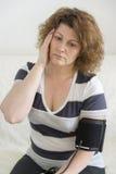 Η γυναίκα με τον πονοκέφαλο μετρά μια πίεση του αίματος Στοκ εικόνες με δικαίωμα ελεύθερης χρήσης