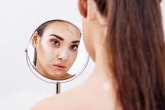 Η γυναίκα με τους μώλωπες ματιών κοιτάζει στην αντανάκλασή της στον καθρέφτη στοκ φωτογραφία