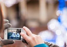 Η γυναίκα με το γάντι παίρνει τη φωτογραφία των αριθμών των χιονανθρώπων στα WI Στοκ Εικόνες