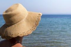 Η γυναίκα με το καπέλο προστατεύει από τον ήλιο στην παραλία Στοκ Εικόνα