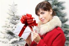 Η γυναίκα με το κιβώτιο δώρων Χριστουγέννων, κοιτάζει μπροστά, με τα δέντρα στο BA Στοκ Φωτογραφίες