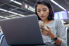 η γυναίκα με το κινητό τηλέφωνο στο χέρι της εργάζεται σε έναν υπολογιστή στοκ φωτογραφία με δικαίωμα ελεύθερης χρήσης