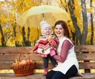 Η γυναίκα με το κορίτσι παιδιών στο πάρκο πόλεων φθινοπώρου κάθεται στον πάγκο με το καλάθι μήλων και την ομπρέλα και την κατοχή  Στοκ Εικόνες