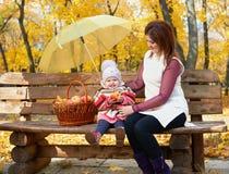 Η γυναίκα με το κορίτσι παιδιών στο πάρκο πόλεων φθινοπώρου κάθεται στον πάγκο με το καλάθι μήλων και την ομπρέλα και την κατοχή  Στοκ Φωτογραφίες