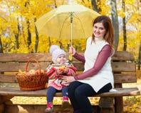 Η γυναίκα με το κορίτσι παιδιών στο πάρκο πόλεων φθινοπώρου κάθεται στον πάγκο με το καλάθι μήλων και την ομπρέλα και την κατοχή  Στοκ εικόνα με δικαίωμα ελεύθερης χρήσης