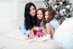Η γυναίκα με το μπλε παιδιών πλέκει τη ζακέτα στο κρεβάτι κοντά στο χριστουγεννιάτικο δέντρο Στοκ Εικόνα