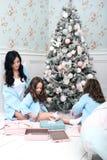 Η γυναίκα με το μπλε παιδιών πλέκει τη ζακέτα στο κρεβάτι κοντά στο χριστουγεννιάτικο δέντρο Στοκ εικόνες με δικαίωμα ελεύθερης χρήσης