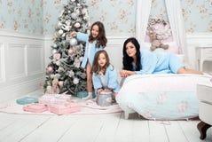 Η γυναίκα με το μπλε παιδιών πλέκει τη ζακέτα στο κρεβάτι κοντά στο χριστουγεννιάτικο δέντρο Στοκ Εικόνες