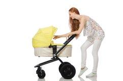 Η γυναίκα με το μωρό και καροτσάκι που απομονώνεται στο λευκό Στοκ φωτογραφία με δικαίωμα ελεύθερης χρήσης